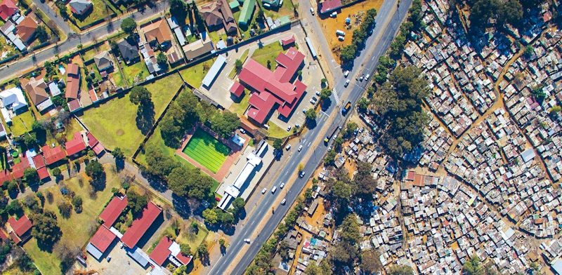 """Aerial image, taken by photographer Johnny Miller, of wealthy Primrose on the left and the informal settlement of Makause on the right. A version of this image made it to the cover of Time magazine, entitled """"The World'sMost Unequal Country"""" in May 2019"""