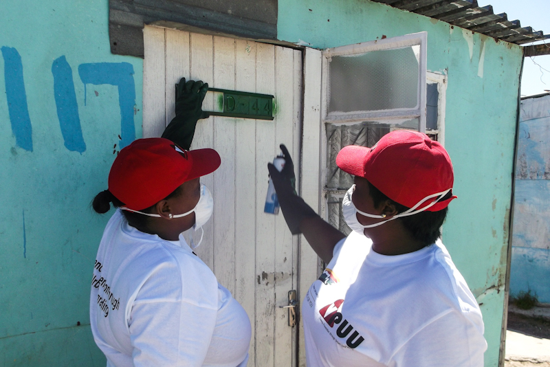 Enumerators with a stencil and spray can physically numbering a structure to be enumerated